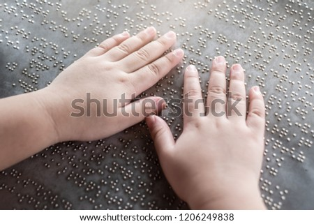 The blind kid's hand and fingers touching the Braille letters on the metal plate to understand an information #1206249838