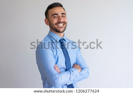 Portrait of joyful professional. Young business man blue shirt and tie crossing arms and smiling at camera. Successful businessman concept #1206277624