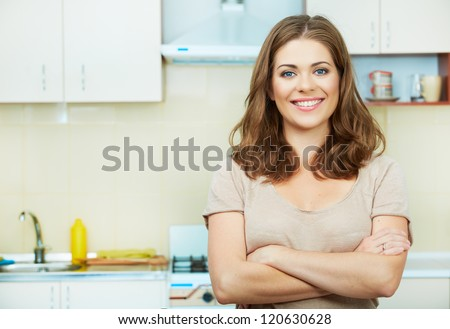 Portrait of young woman with arms crossed standing against kitchen interior background. #120630628