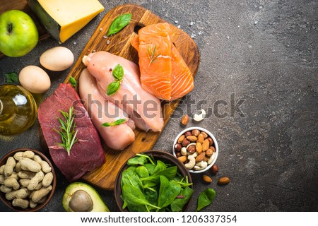 Ketogenic low carbs diet. Meat, fish, nuts,  oil, cheese, milk and avocado on dark stone background. Top view with copy space. #1206337354