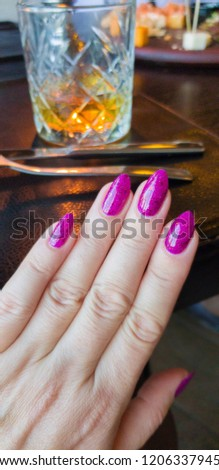Female hand with purple long nails and nail polish bottle #1206337945