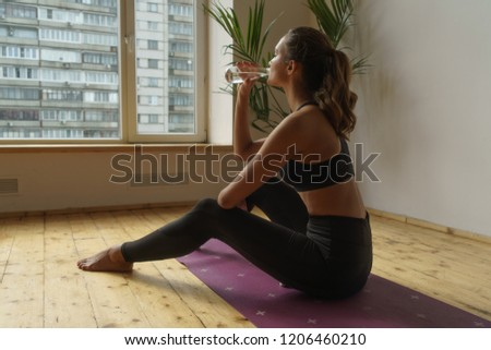 young sportive woman sitting on yoga carpet and drinking clear water at home #1206460210
