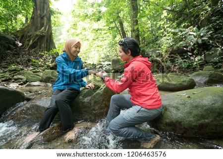Selangor, Malaysia – July 21, 2018: Man making marriage proposal to his girlfriend on the forest. Lovers against seascape. Traveling couple in love on forest. #1206463576