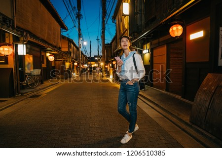 full length photo of a beautiful lady standing on the dark street with many lanterns hanging on roof. Woman texting instant messaging text on mobile phone online at night. Japanese lady lifestyle.