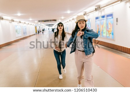 asian sisters are in a rush to catch the train. female travelers running in the passageway in the railway station. backpacker self-guided trip in USA concept. #1206510430