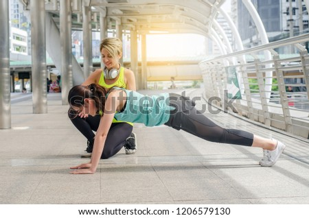 Two attractive sport girls smiling while working out and doing plank exercise in fitness class in street city #1206579130