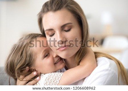 Cute little girl hug young mom, touching her face, showing love and care, millennial mother embrace small daughter, feeling sweet tender moment, enjoying time together. Family relationships concept #1206608962