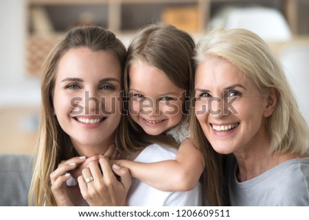 Close up portrait of happy three generations of women hugging enjoying time together at home, smiling mother, daughter and grandmother embrace having fun and laughing, posing for family picture #1206609511