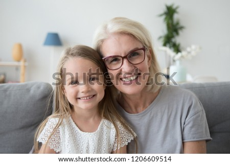 Portrait of smiling cute little girl posing with grandma hugging and cuddling at home, happy grandmother and granddaughter spend time together look at camera making family picture