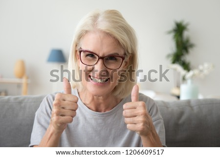 Excited mature woman in glasses sit on couch at home showing thumbs up satisfied with service, smiling elderly female make like gesture recommending something, satisfied with choice or decision #1206609517