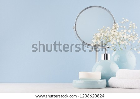 Delicate elegant ceramic decorations for bathroom - soft blue bowls, vase, white flowers, towel and soap on white wood table. Modern bath interior. #1206620824