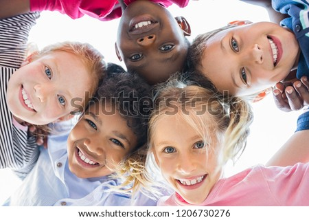 Closeup face of happy multiethnic children embracing each other and smiling at camera. Team of smiling kids embracing together in a circle. Portrait of young boy and pretty girls looking at camera. #1206730276