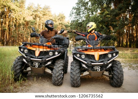 Two atv riders hits fists for good luck, back view #1206735562