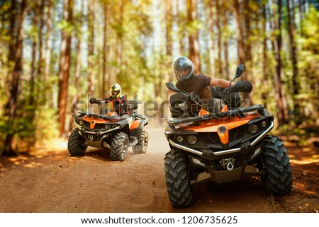 Two atv riders, speed race in forest, front view #1206735625