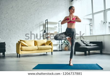 Attractive young woman in sportswear is doing yoga at home. #1206737881