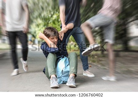 Aggressive teenagers bullying boy outdoors, view with motion blur effect Royalty-Free Stock Photo #1206760402