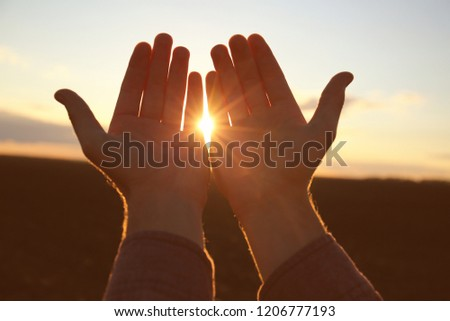 Hands of religious man praying outdoors at sunset #1206777193
