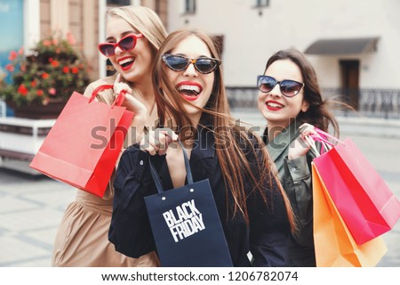 Stylish slim ladies wearing trench-coat and sunglasses walking with colorful shopping bags near the store during shopping process, concept of consumerism, sale, rich life #1206782074