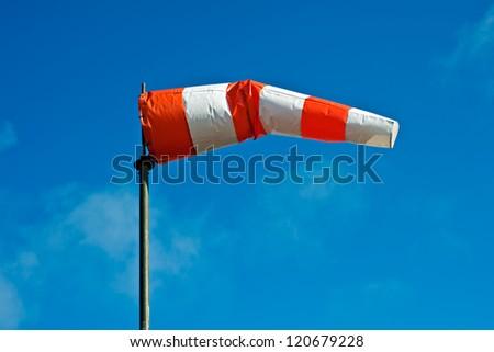 wind sock against a blue sky #120679228