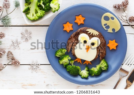 Fun food for kids - cute little penguin made of a meat hamburger or ground meat pattie with broccoli for a healthy dinner for children. Creative cooking idea #1206831643
