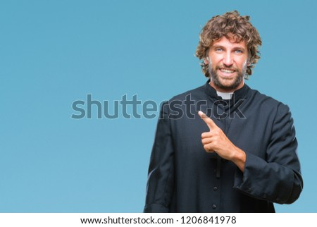 Handsome hispanic catholic priest man over isolated background cheerful with a smile of face pointing with hand and finger up to the side with happy and natural expression on face #1206841978