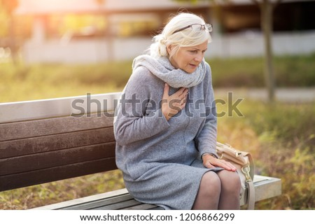 Senior Woman Suffering From Chest Pain While Sitting On Bench Royalty-Free Stock Photo #1206866299