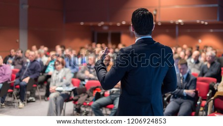 Speaker giving a talk on corporate business conference. Unrecognizable people in audience at conference hall. Business and Entrepreneurship event. #1206924853