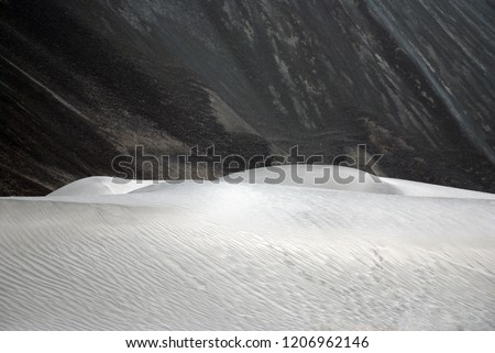 Nature Scene of white Sand dune and Gray mountain background at Hunder Sand dune Nubra Valley , Leh Ladakh , India #1206962146