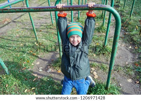 A little boy is hanging on the bar, looking at us and smiling. Exercise in the fresh air. Useful education for health. Development of physical strength, dexterity, endurance. #1206971428
