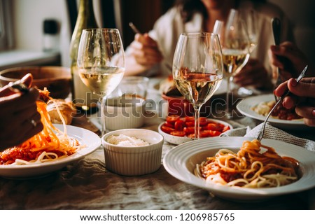 Friends having a pasta dinner at home of at a restaurant. #1206985765
