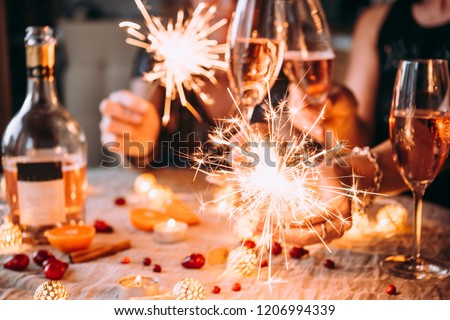 Friends celebrating Christmas or New Year eve party with Bengal lights and rose champagne. Royalty-Free Stock Photo #1206994339