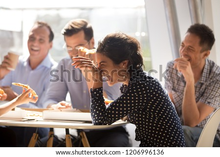 Indian woman laughing at funny joke eating pizza with diverse coworkers in office, friendly work team enjoying positive emotions and lunch together, happy colleagues staff group having fun at break #1206996136