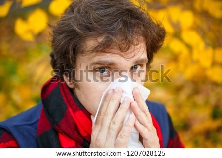 Man with cold rhinitis on autumn background. Fall flu season. Ill sick sneezing male. Handkerchief, vaccine against influenza virus Caught Cold Headache Allergy runny nose #1207028125