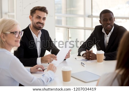 Interested diverse workers sit at table listen to female colleague talking, multiethnic business people look at employee share thoughts at briefing, curious mixed coworkers discuss project at meeting #1207034419