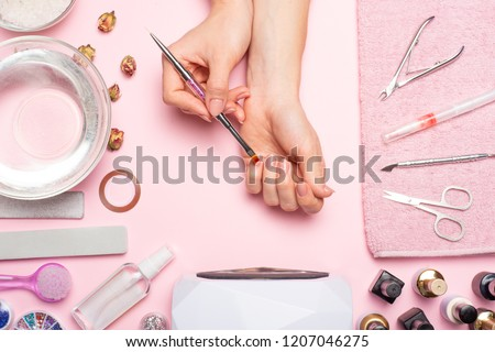 Nail care. beautiful women hands making nails painted with pink gentle nail polish on a pink background. Women's hands near a set of professional manicure tools. Beauty care #1207046275