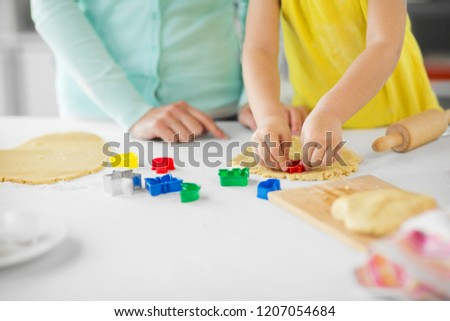 family, cooking and people concept - mother and little daughter with molds making cookies from dough at home kitchen #1207054684