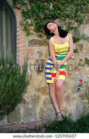 Beautiful young woman is posing on the old brick wall, Tuscan, Italy. Warm evening light #120705637