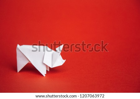 Chinese Zodiac Sign Year of Pig. green origami paper tree and white pig symbol of 2019, on a red background, free space for text, minimalism. Happy New Year 2019 year #1207063972