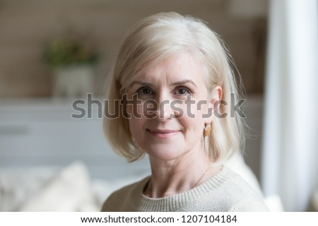 Close up portrait of happy aged beautiful female looking at camera relaxing at home, smiling senior woman posing for picture or photo, elderly lady feeling positive shoot for album in country house