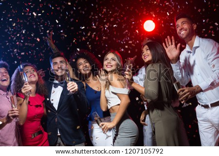 New Year party. Group of friends smiling and shaking hands upwards, nightclub reportage #1207105792