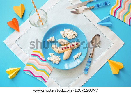 Fun food idea for kids. children's Breakfast: plane made of banana and clouds made of curd on a blue plate. dreams of flying. creative lunch of the future pilot. #1207120999