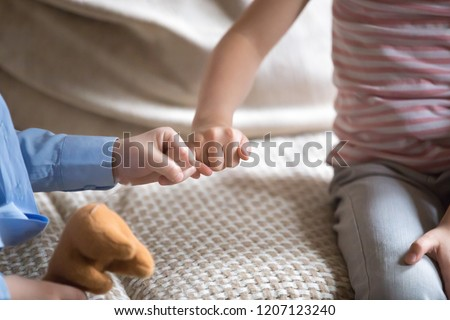 Small kids sitting on couch at home little children reconciling after fight or quarrelling making peace with fingers gesture joining pinkies symbol of no more arguing swear be friends forever concept