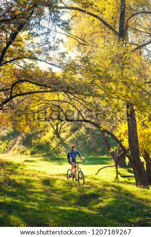 Biking in the forest. Girl rides a bike on a forest trail. Woman riding her bike in the park. Bicycle touring. Travel to scenic places. Autumn trees. #1207189267