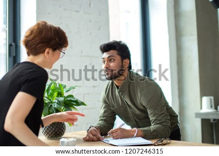 Two business people discuss meeting at table with documents and write notes #1207246315