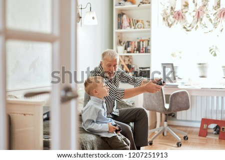 Cute little boy with grandfather sitting on sofa and playing video game with game pad #1207251913