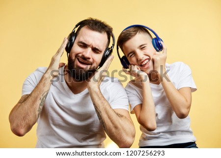 Bearded father and his son in headphones listen to music on yellow background #1207256293