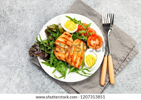 Grilled chicken breast. Fried chicken fillet and fresh vegetable salad of tomatoes, mangold and arugula leaves. Chicken meat salad. Healthy food. Flat lay. Top view. Gray background #1207313851