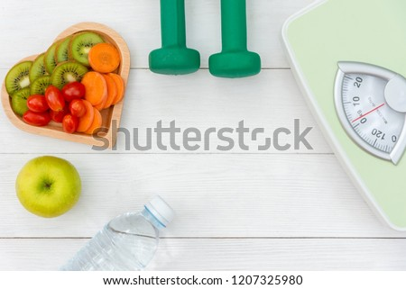 Diet and weight loss for women healthy care with  weight scale and fitness equipment,fresh water and vitamins fruit healthy, apple, banana, carrot white wooden background top view.  Healthy Concept.  #1207325980