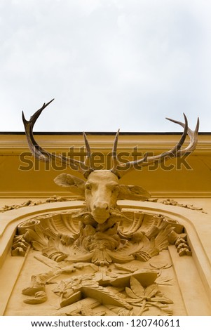 A stone deer head with real antlers on a wall of a noble building #120740611