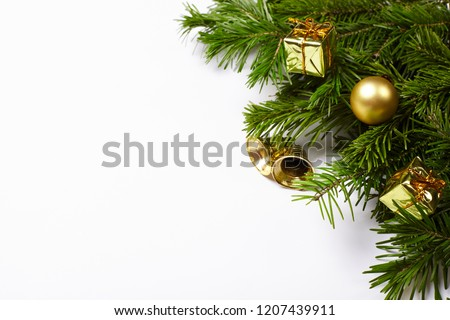 Christmas tree branches and golden decorations on white background. New year frame.